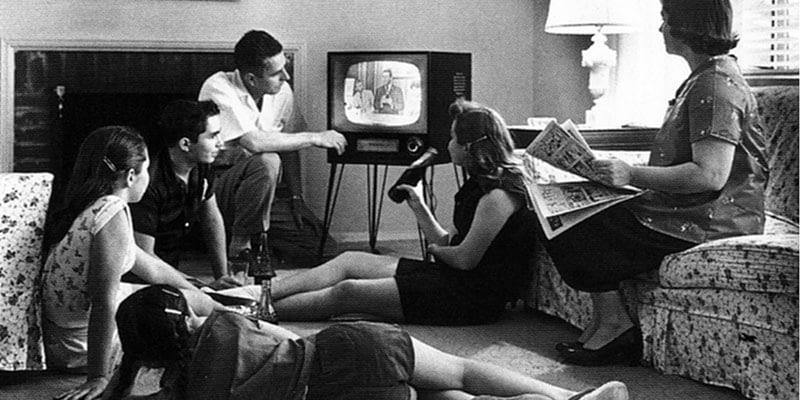 Människor runt en TV på femtiotalet